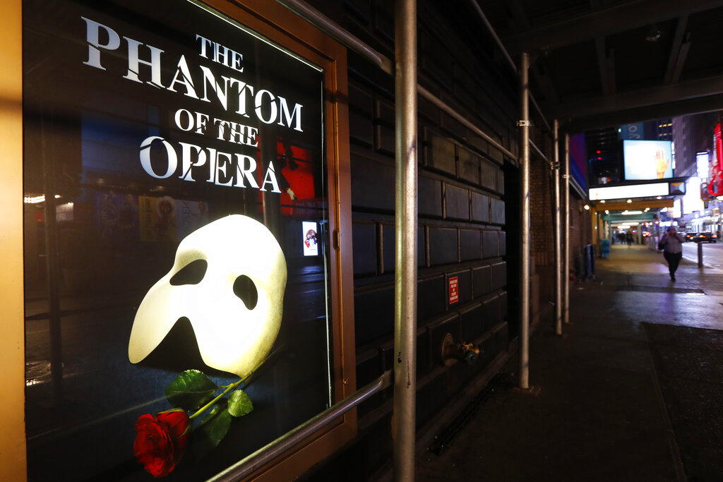 """In this March 12, 2020, file photo, a poster advertising """"The Phantom of the Opera"""" is displayed on the shuttered Majestic Theatre in New York. (AP Photo/Kathy Willens)"""