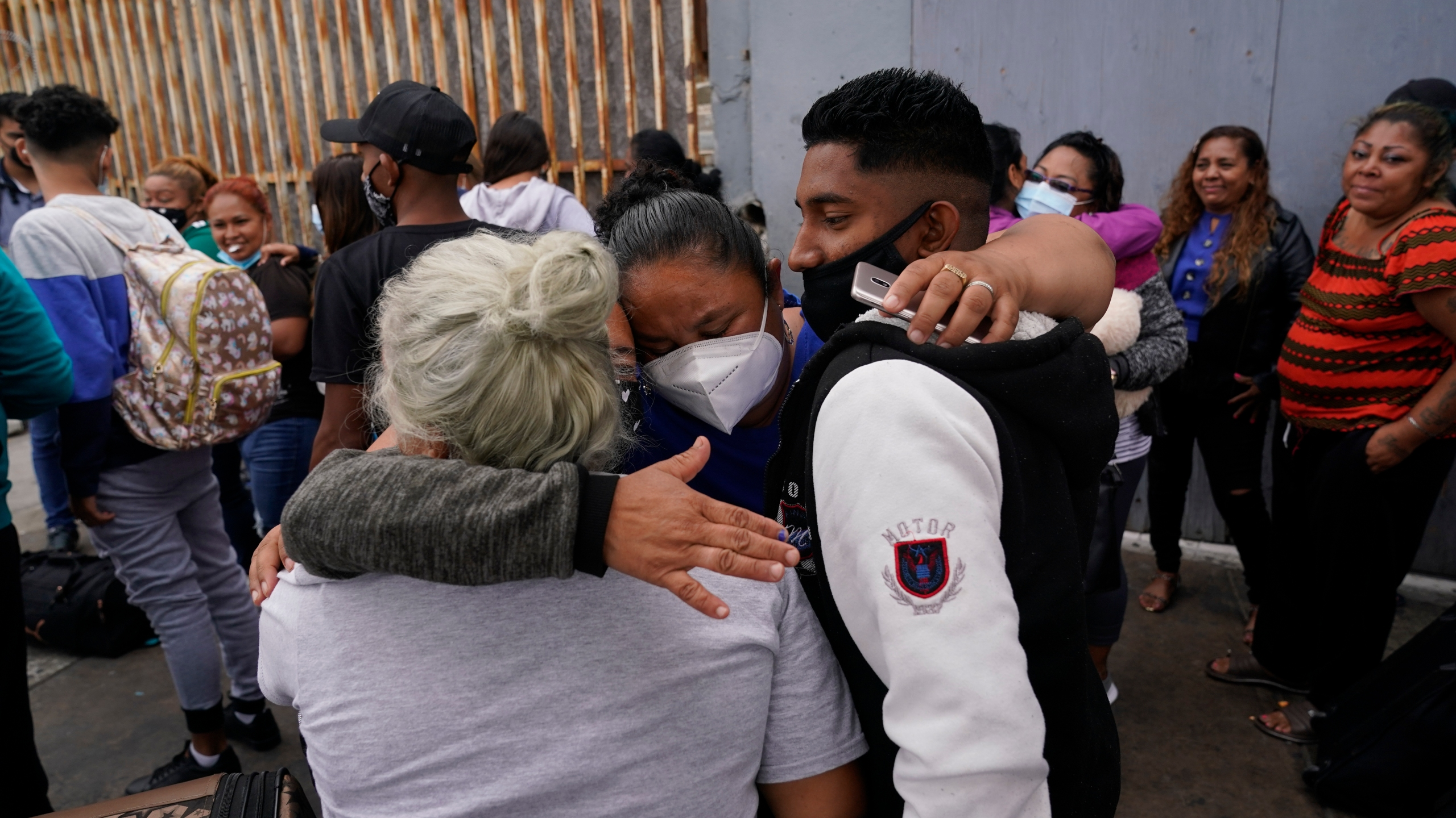 In this July 5, 2021, file photo, Alex Cortillo, right, of Honduras gets a hug from Erika Valladares Ponce, of Honduras, center, and others, as he waits to cross into the United States to begin the asylum process in Tijuana, Mexico. Two nongovernmental organizations said Friday, July 30, 2021, that they are ending cooperation with the Biden Administration to identify the most vulnerable migrants waiting in Mexico to be admitted to the United States to seek asylum. (AP Photo/Gregory Bull, File)