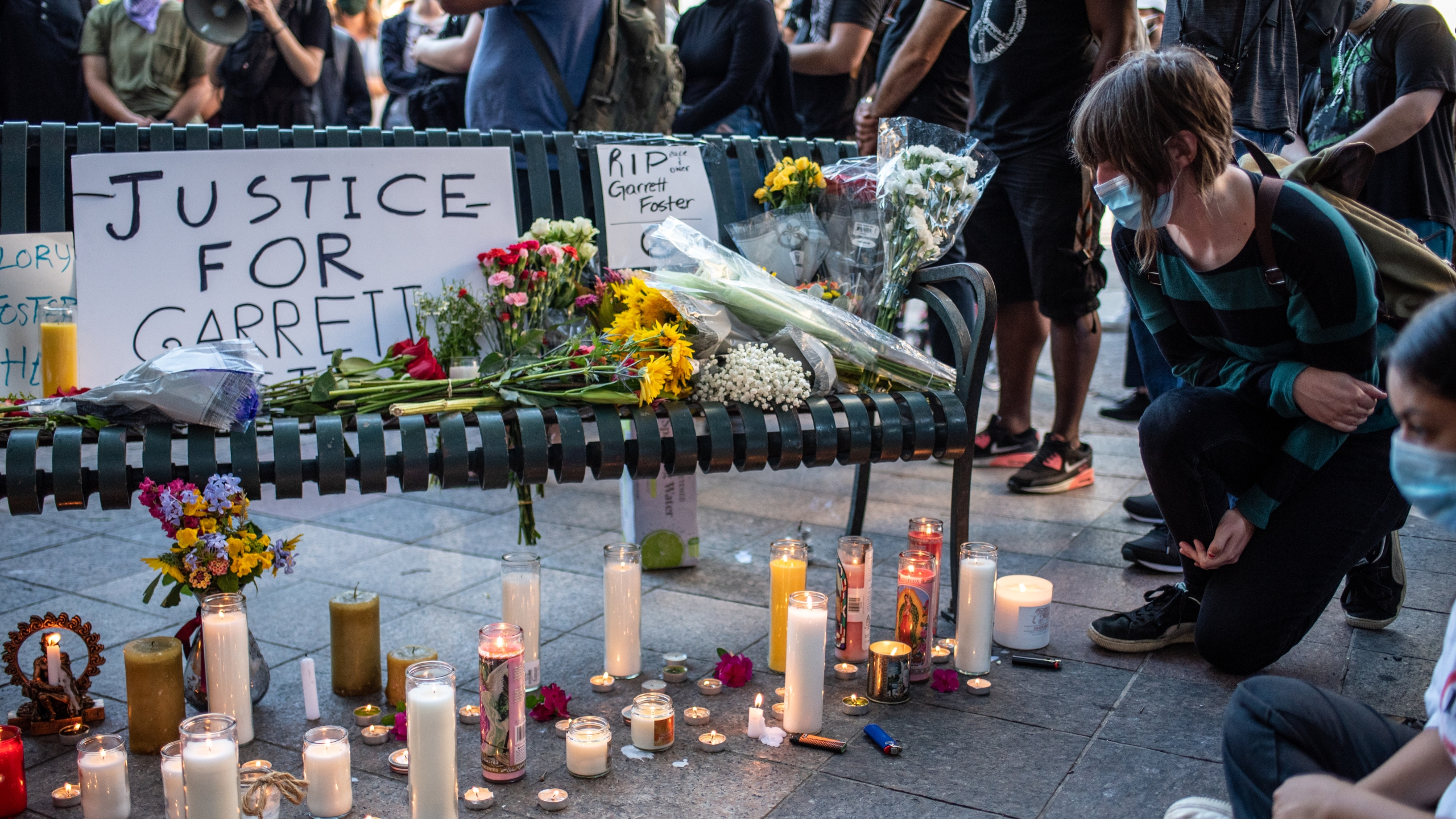 An attendee kneels at a memorial at a vigil for Garrett Foster on July 26, 2020 in downtown Austin, Texas. (Sergio Flores/Getty Images)