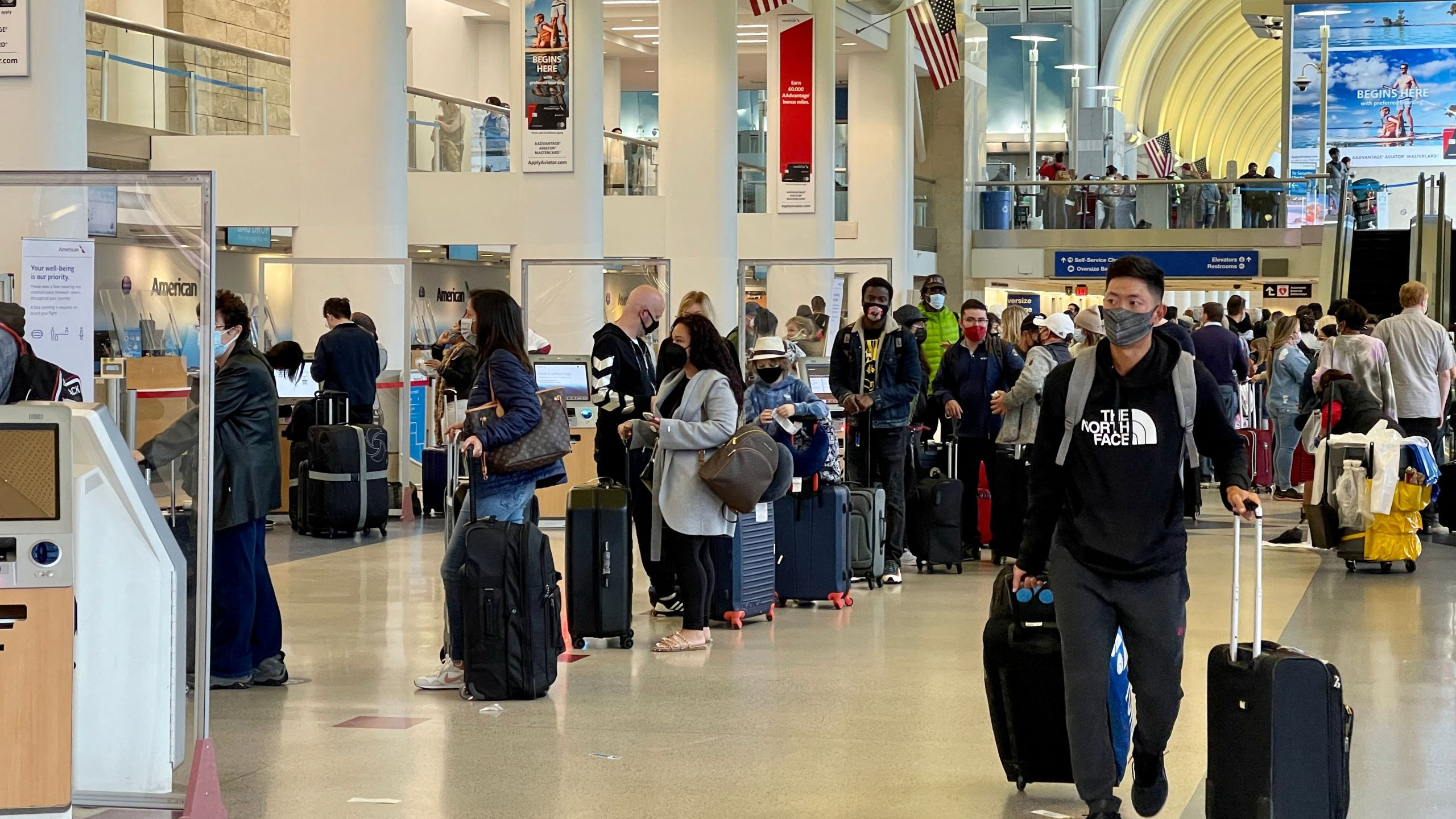 Passengers wait in line at the American Airlines checkin counters at the Los Angeles International Airport (LAX) on April 24, 2021. (DANIEL SLIM/AFP via Getty Images)