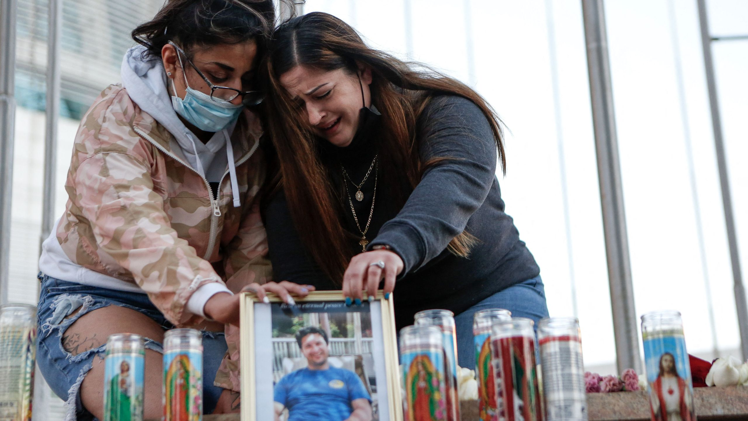 Two women mourn their cousin as they attend a vigil for the victims of a shooting at San Jose City Hall on May 27, 2021. (AMY OSBORNE/AFP via Getty Images)