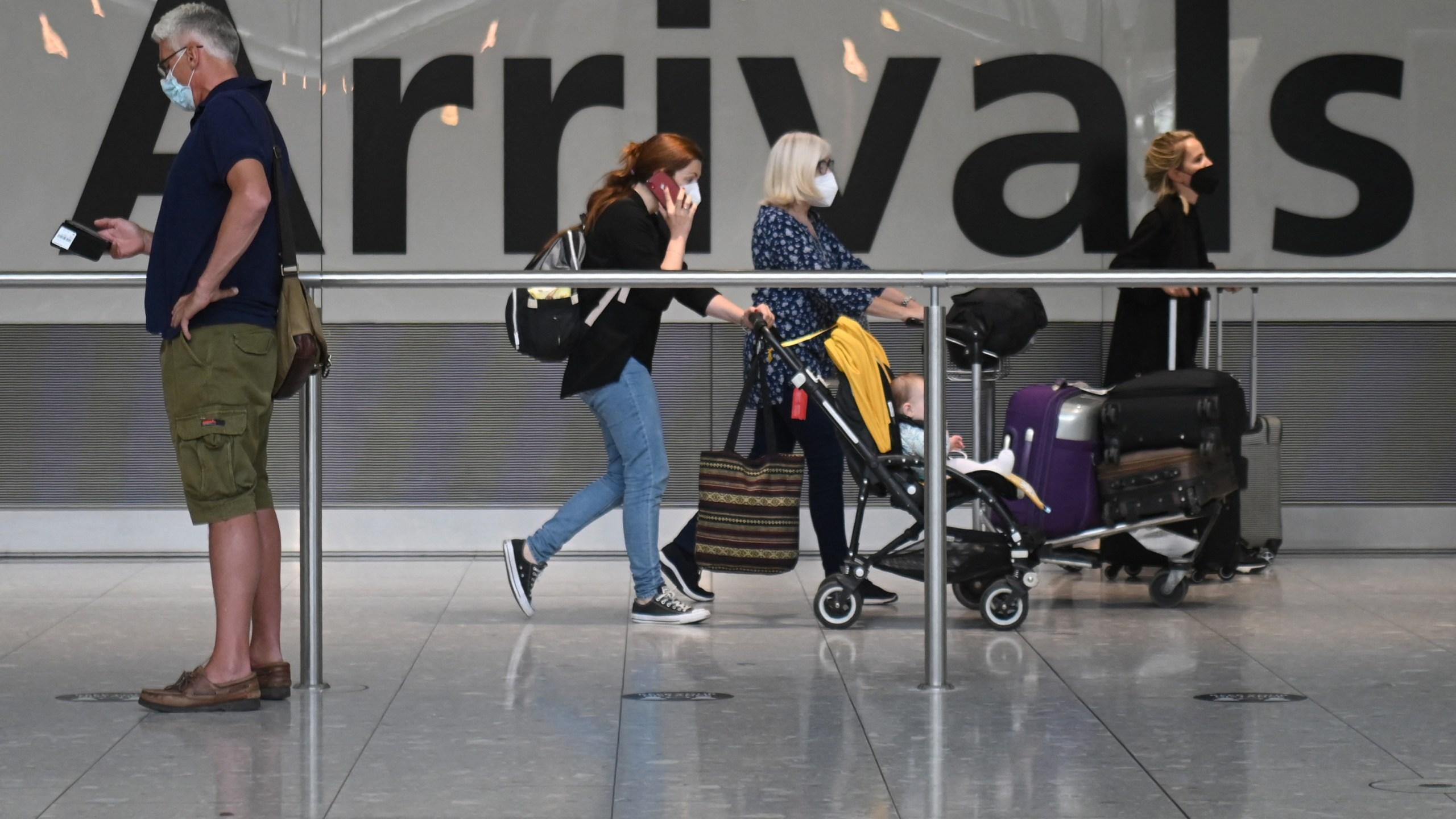 Travelers walk through Heathrow airport in London, on June 3, 2021. (DANIEL LEAL-OLIVAS/AFP via Getty Images)
