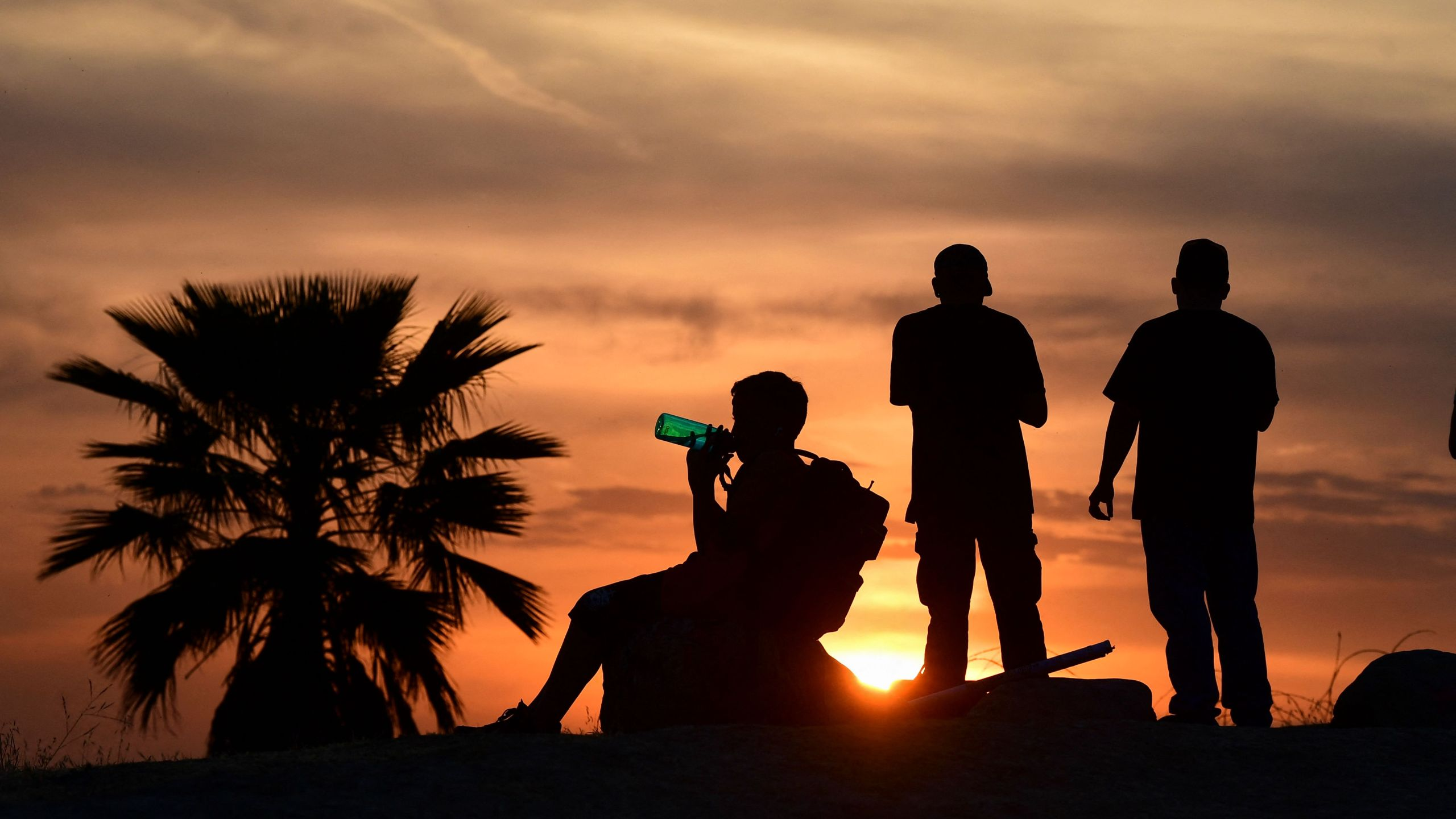 People view the sun set as a child drinks from a water bottle on June 15, 2021 in Los Angeles, as temperatures soar in an early-season heatwave. (Frederic J. BROWN/AFP via Getty Images)