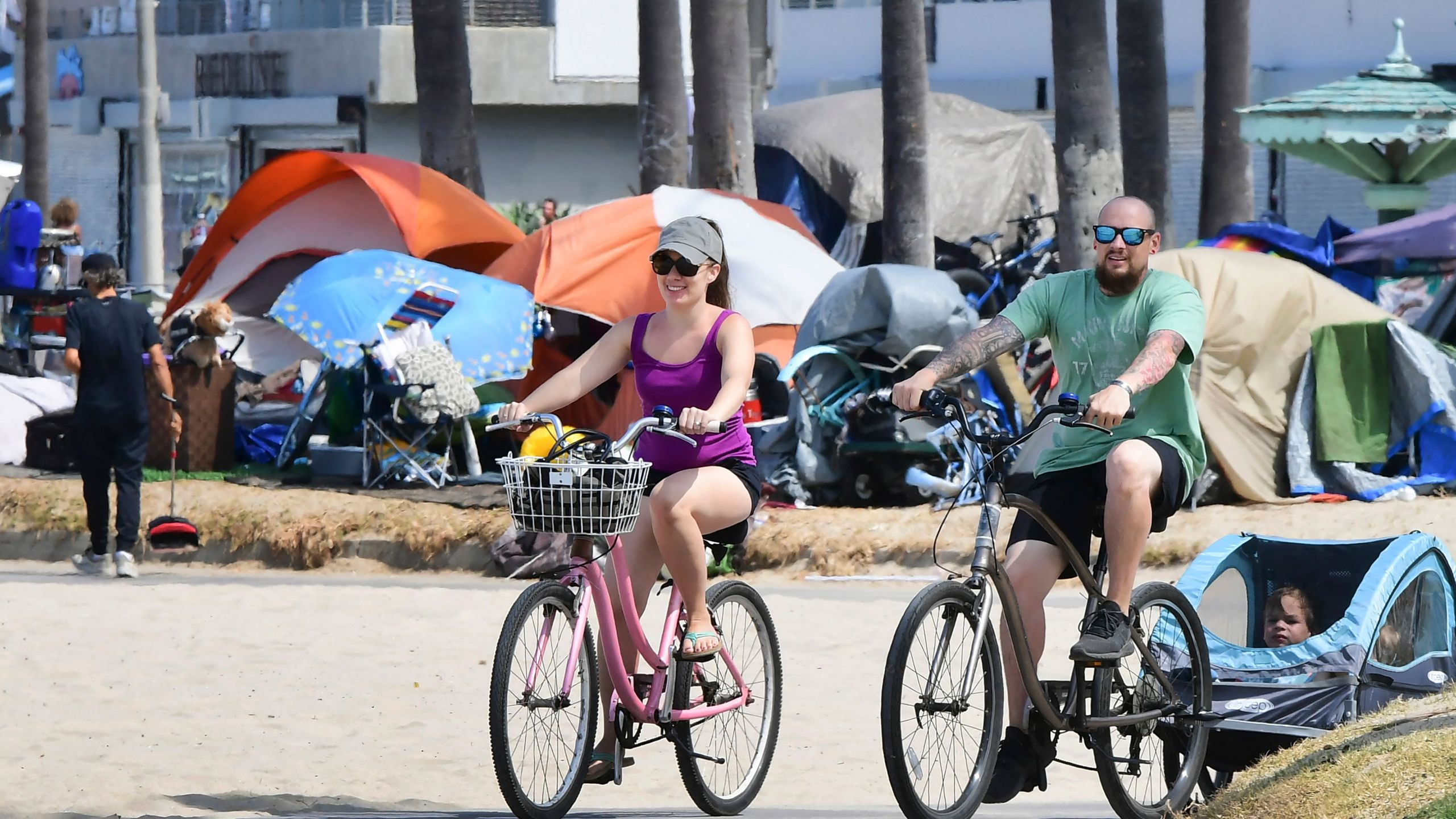 Cyclists ride past tents housing the homeless along the Ocean Front Walk in Venice, California on June 30, 2021, where an initiative began this week offering people in homeless encampments a voluntary path to permanent housing. (Frederic J. Brown AFP via Getty Images)