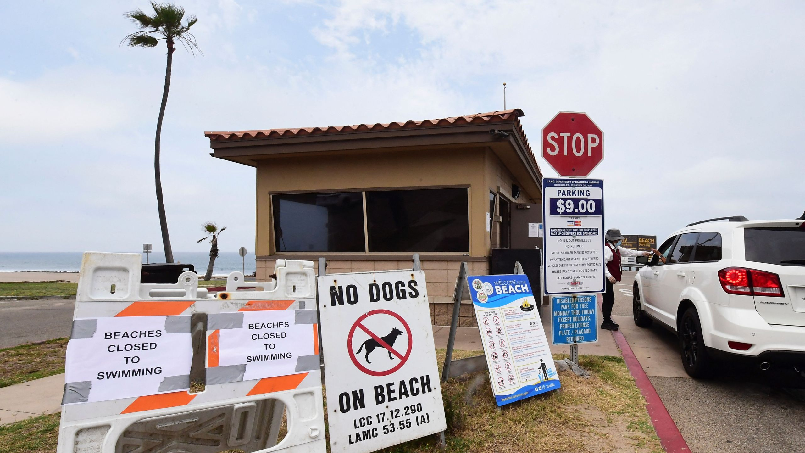 Signs posted at the entrance to Dockweiler State Beach indicate that the beach is closed to swimming after a sewage spill in Playa del Rey, in Los Angeles County, California, on July 13, 2021. (Frederic J. Brown/AFP via Getty Images)