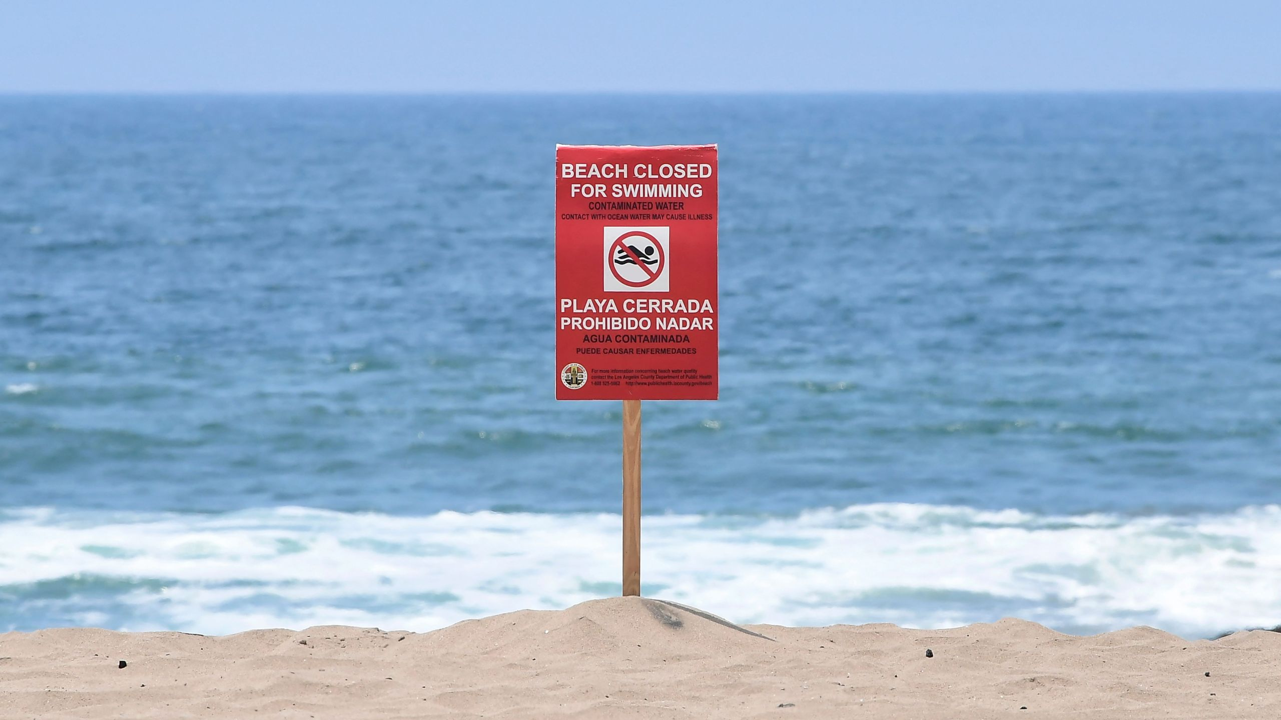 A sign indicates that the Dockweiler State Beach is closed to swimming after a sewage spill in Playa del Rey, in Los Angeles County, California, on July 13, 2021. (FREDERIC J. BROWN/AFP via Getty Images)