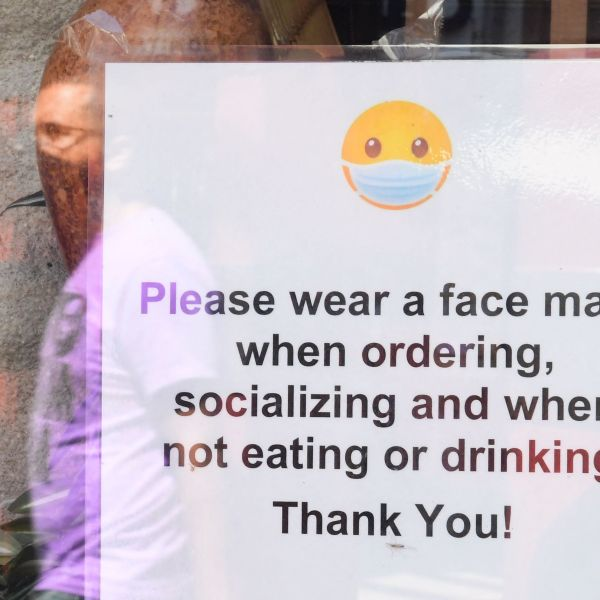 A Los Angeles storefront sign reminds people to wear a facemask on July 19, 2021. (FREDERIC J. BROWN/AFP via Getty Images)