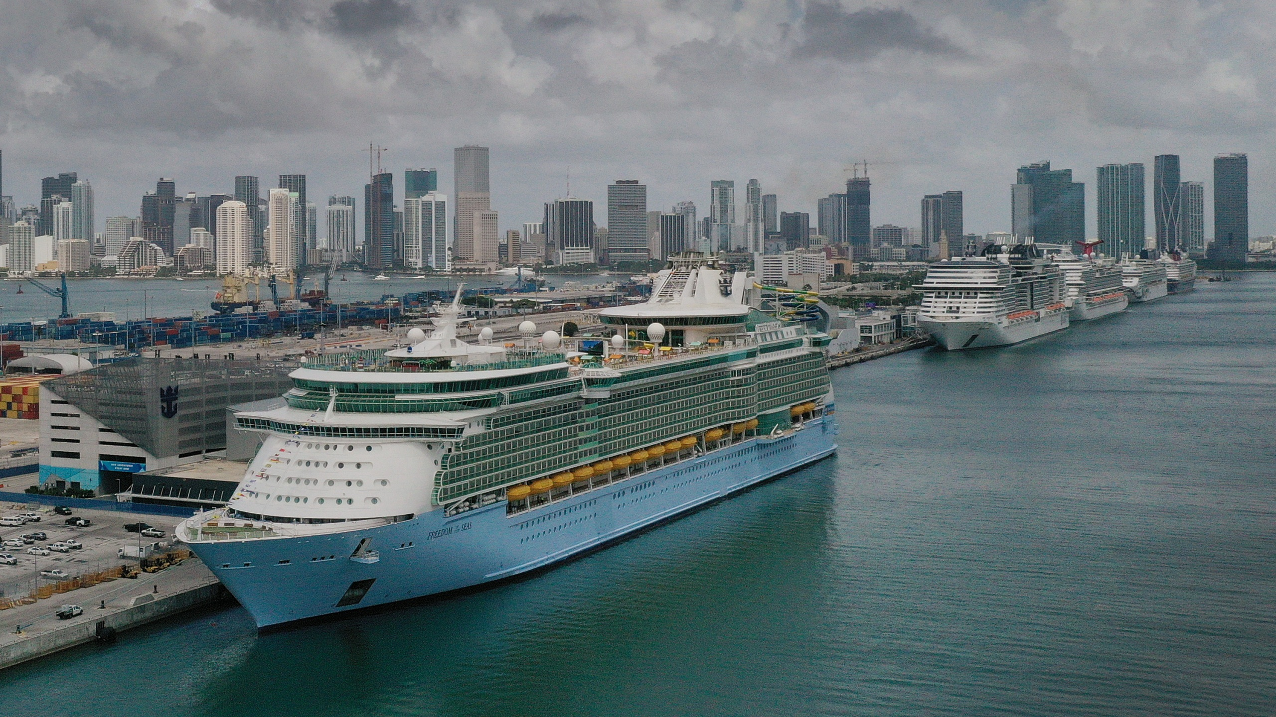 In an aerial view, the Royal Caribbean Freedom of the Seas (L) prepares to set sail from PortMiami during the first U.S. trial cruise testing COVID-19 protocols on June 20, 2021 in Miami, Florida. (Joe Raedle/Getty Images)