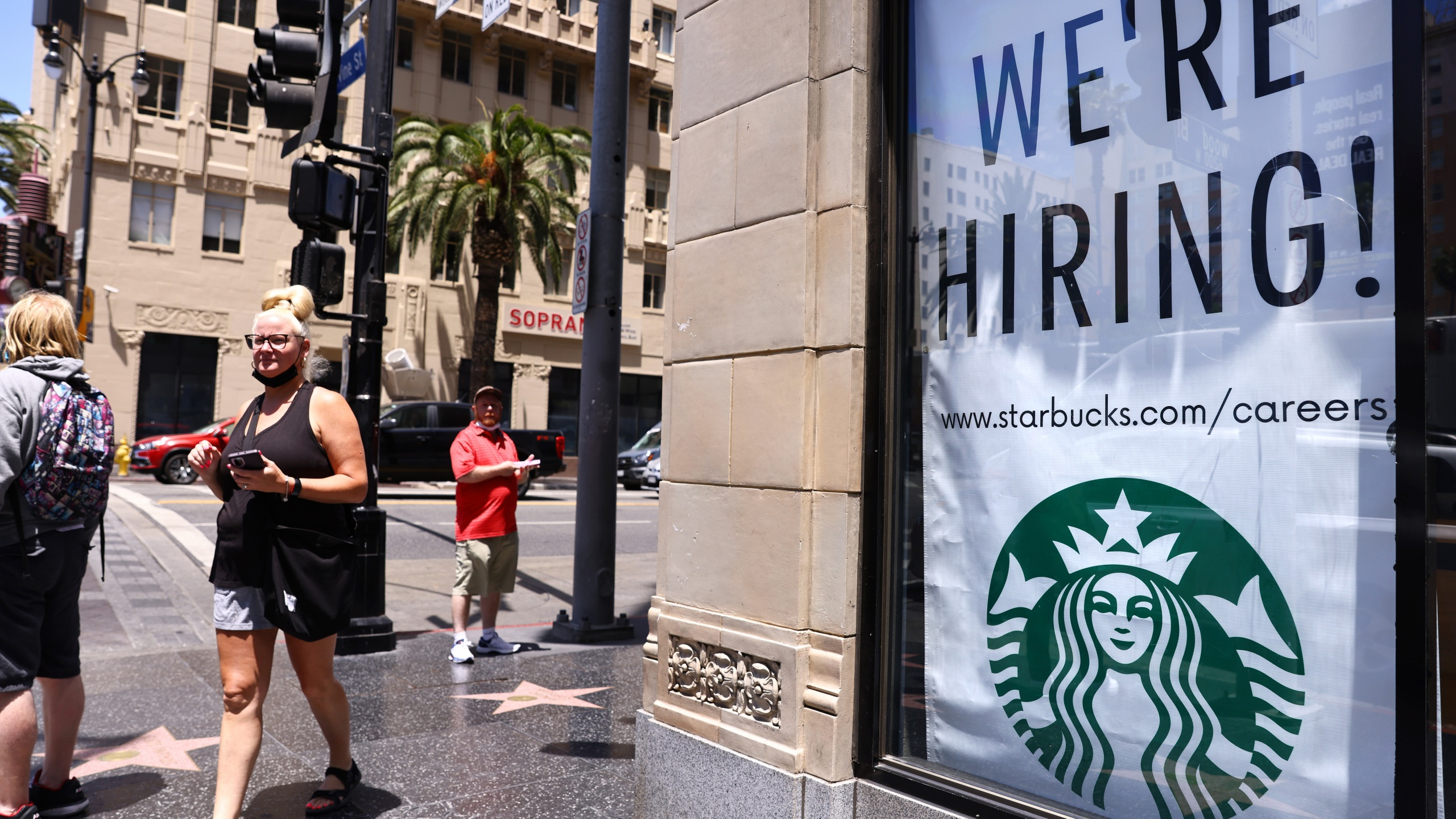 A 'We're Hiring!' sign is displayed at a Starbucks on Hollywood Boulevard on June 23, 2021 in Los Angeles. (Mario Tama/Getty Images)