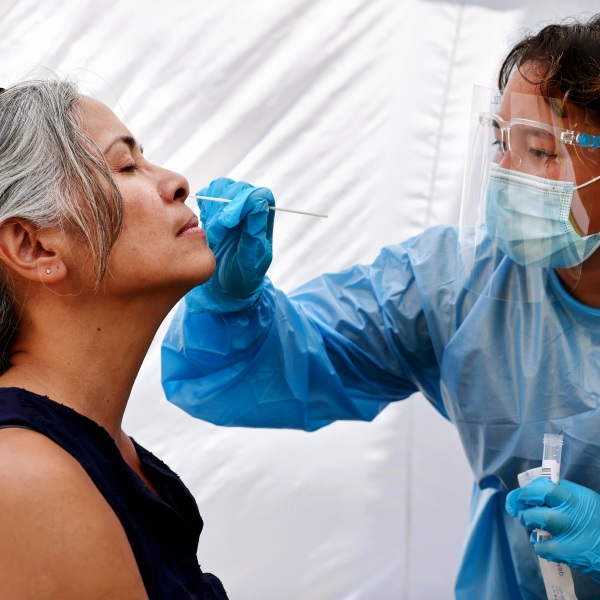 A medical assistant administers a COVID-19 test to a person at Sameday Testing in Los Angeles on July 14, 2021. (Mario Tama / Getty Images)