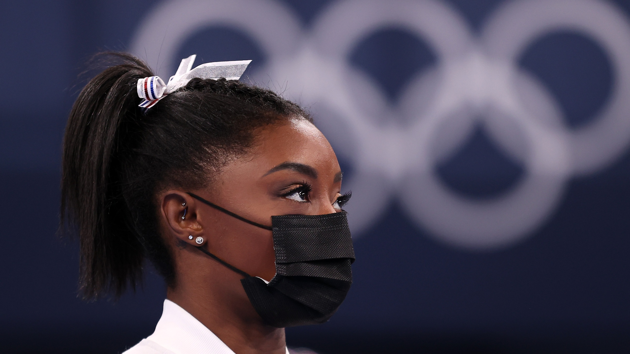 Simone Biles of Team United States watches her team perform on bars after pulling out of the competition after only competing on the vault during the Women's Team Final on day four on day four of the Tokyo 2020 Olympic Games at Ariake Gymnastics Centre on July 27, 2021, in Tokyo, Japan.(Laurence Griffiths/Getty Images)