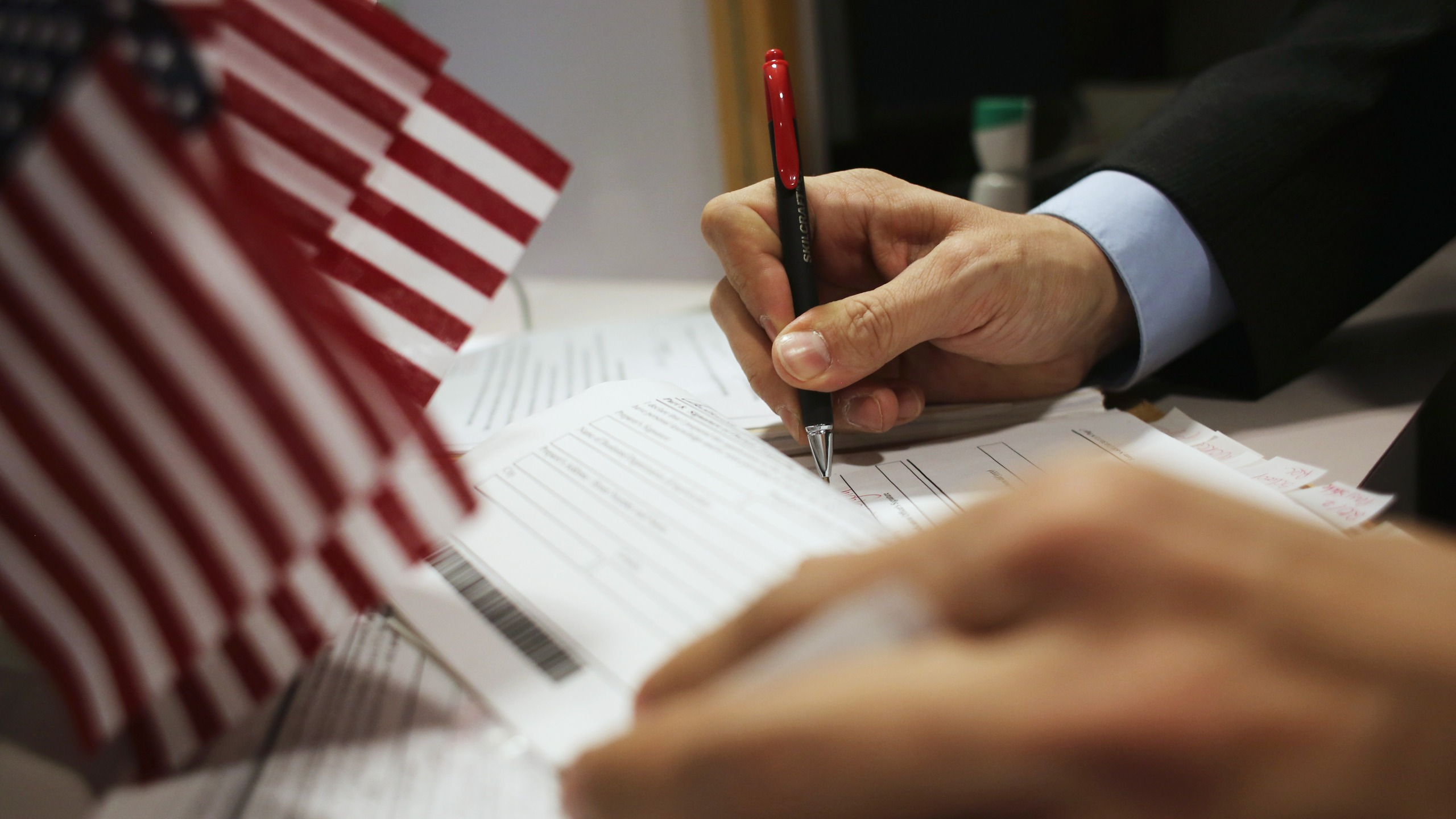 This file photo shows an official signing applications at the U.S. Citizenship and Immigration Services district office on Jan. 29, 2013, in New York City. (John Moore/Getty Images)