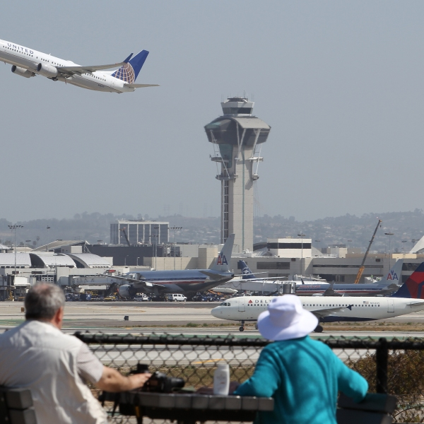 This file photo shows people watching as a jet passes the air traffic control tower at Los Angles International Airport on April 22, 2013 in Los Angeles. (David McNew/Getty Images)
