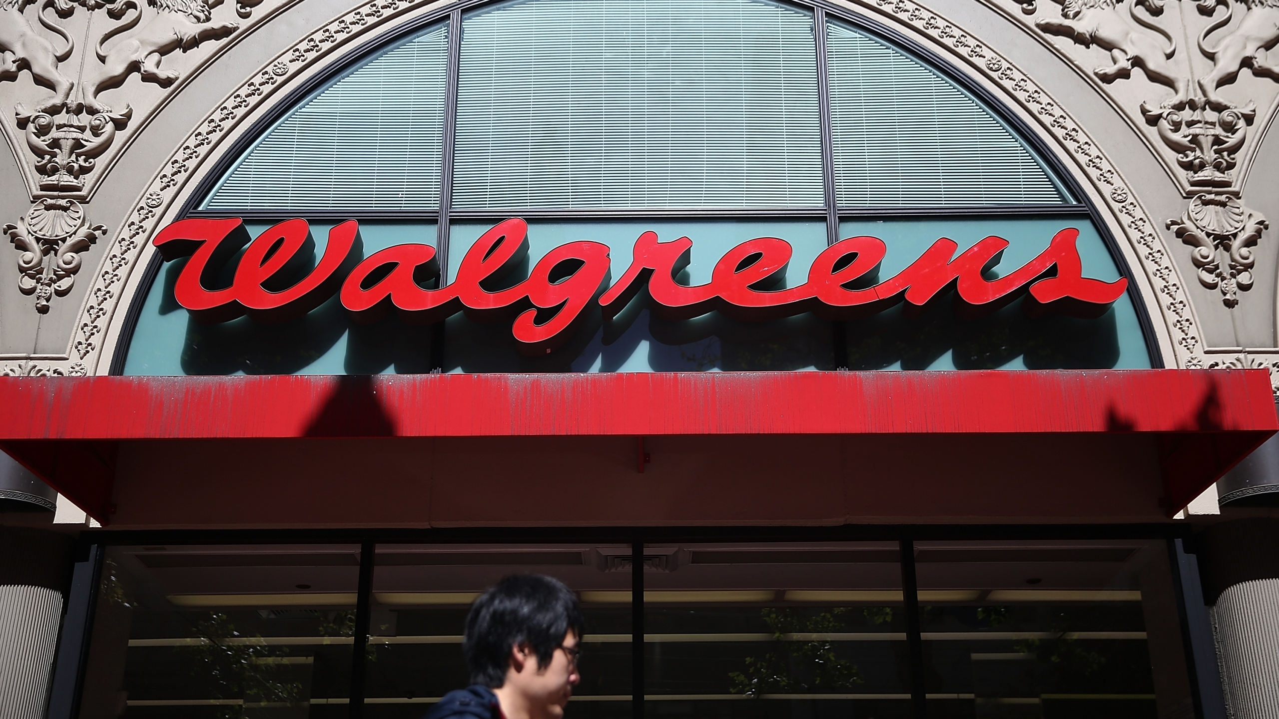 This file photo shows a pedestrian walking by a Walgreens store in San Francisco on April 5, 2016. (Justin Sullivan/Getty Images)
