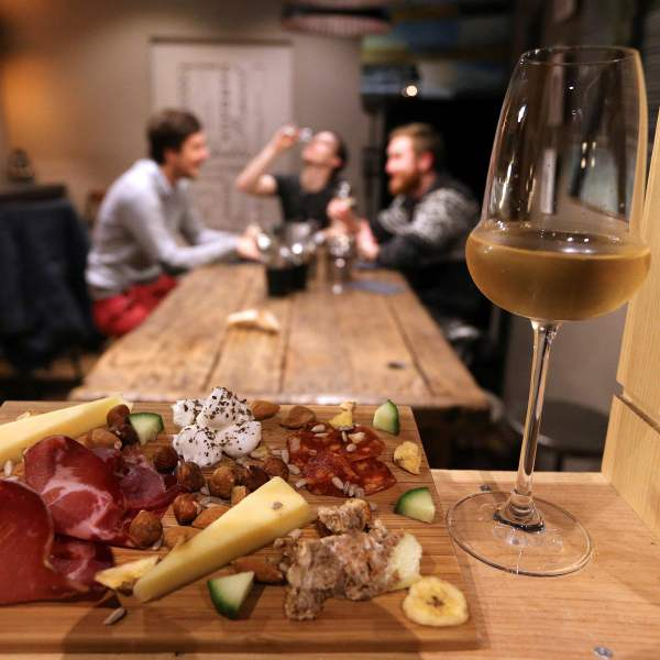 A glass of champagne is served with cheese and ham as guests sit together at a table at the bar 'Aux 3 p'tits bouchons' in Reims, northeastern France, on December 20, 2016. (FRANCOIS NASCIMBENI/AFP via Getty Images)