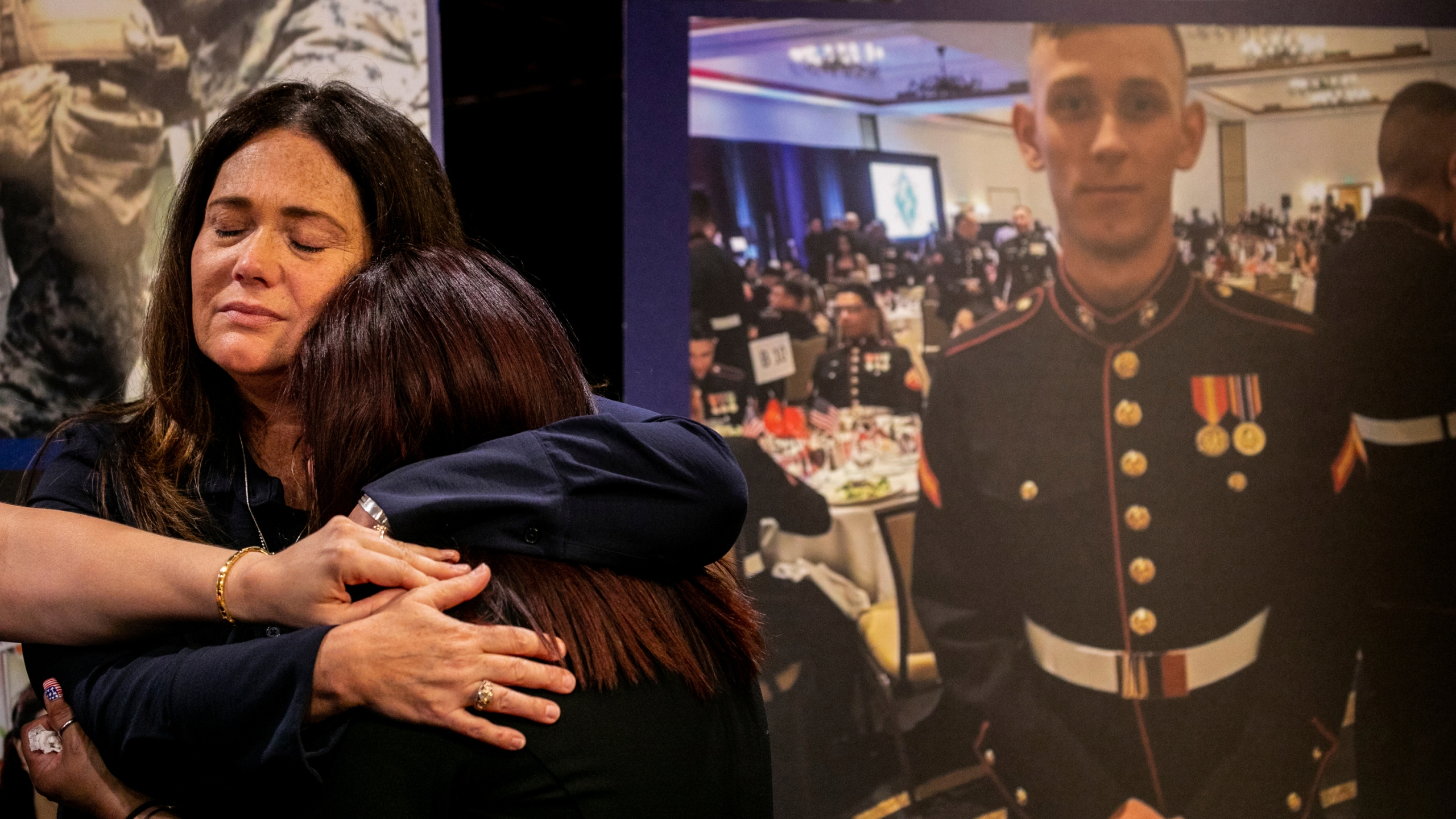 Christiana Sweetwood, mother of Marine Lance Corporal Chase Sweetwood, hand coming from left, Aleta Bath, mother of Private First Class Evan Bath and Lupita Garcia, mother of Marine Lance Corporal Marco Barranco embrace each other at a press conference next to a picture of Chase Sweetwood July 29, 2021, in Oceanside, Calif. (Sam Hodgson/The San Diego Union-Tribune via AP)