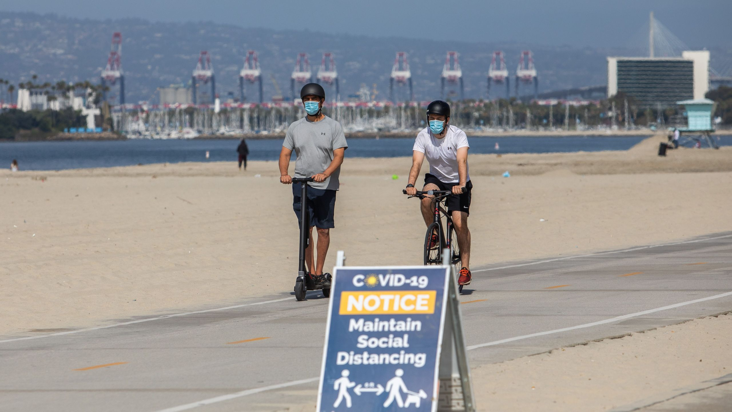 Men wearing facemasks ride a scooter and a bike near a notice about maintaining social distance on the beach in Long Beach on July 14, 2020. (APU GOMES/AFP via Getty Images)