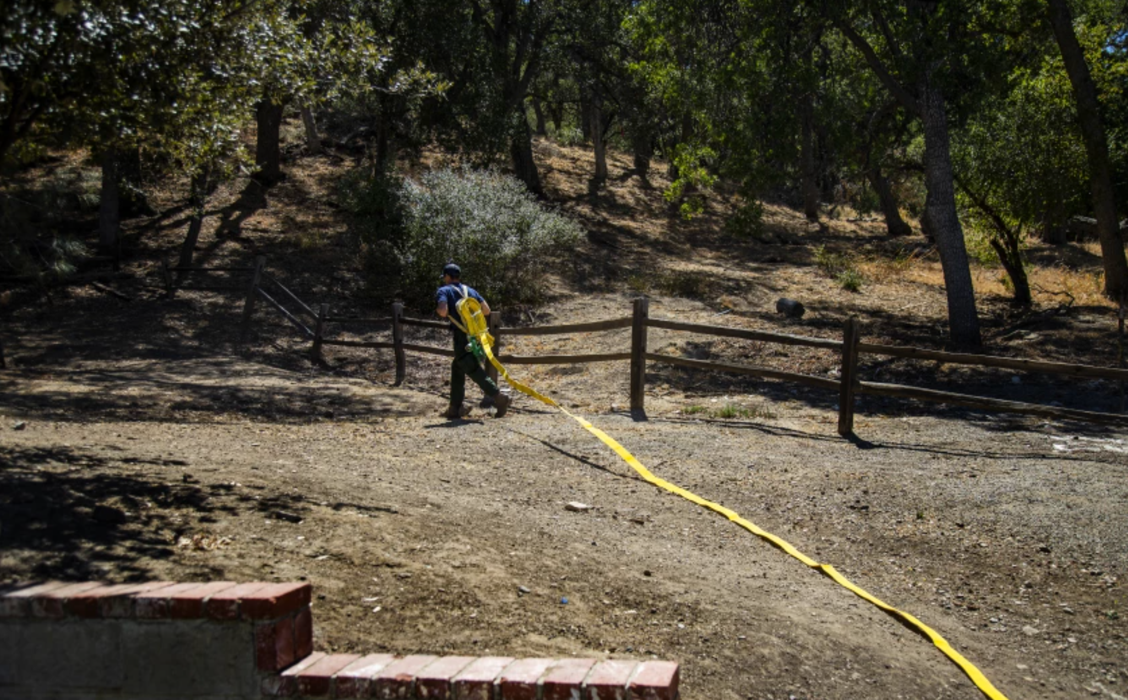 """U.S. Forest Service firefighter Nick Browne deploys a fire hose pack during training in Castaic. Crews in the bone-dry forest must aim for 100% mop-up, meaning they must extinguish every ember. """"There are no shortcuts here,"""" he said.(Gina Ferazzi / Los Angeles Times)"""
