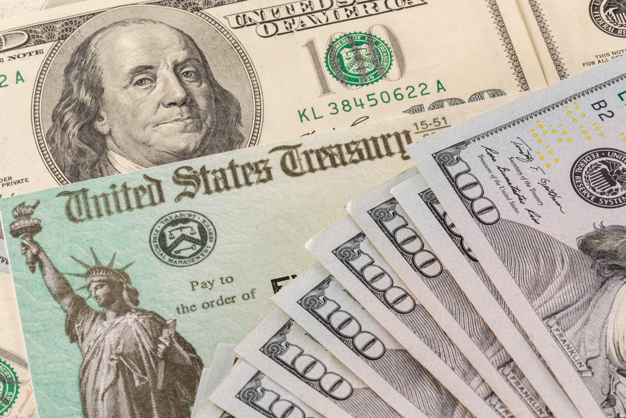 A stimulus check and cash are seen in a file photo. (iStock/Getty Image Plus)