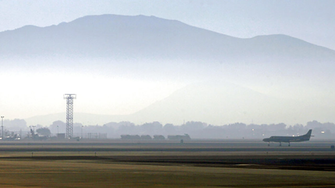 In this Sept. 24, 2014 file photo, smoke hangs over Reno-Tahoe International Airport as a plane takes off in Reno, Nev. (AP Photo/Martha Irvine, File)