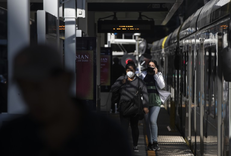 Metro Blue Line riders exit a train at Pico station on March 26, 2020. (Brian van der Brug / Los Angeles Times)