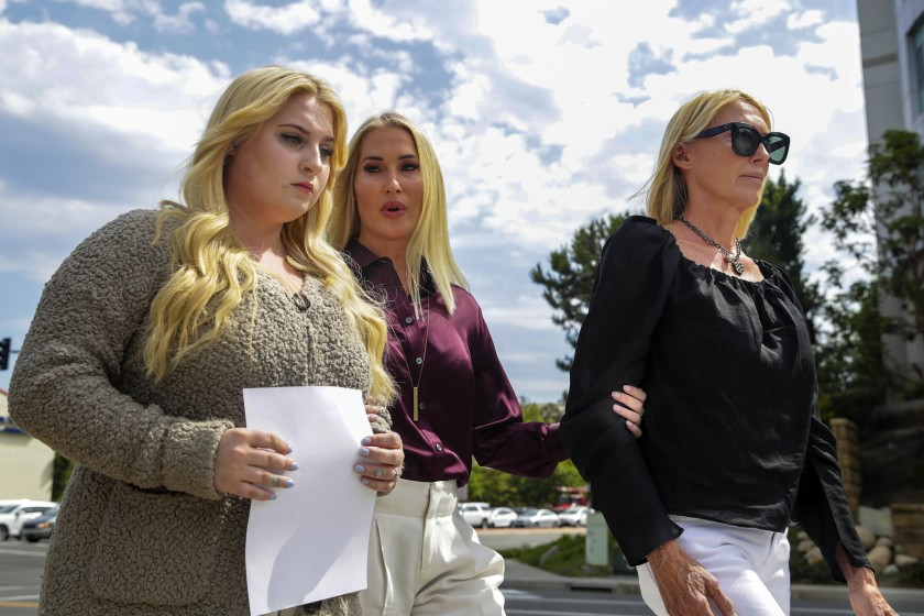 Zoe Cooksey, left, walks with her mother, Amber Leight, center, and grandmother, Annette Oltmans, outside Providence Mission Hospital in Mission Viejo on July 8, 2021. Cooksey has filed a lawsuit against the hospital's parent company and former nurse Paul Alden Miller, alleging he sexually assaulted her.(Irfan Khan / Los Angeles Times)
