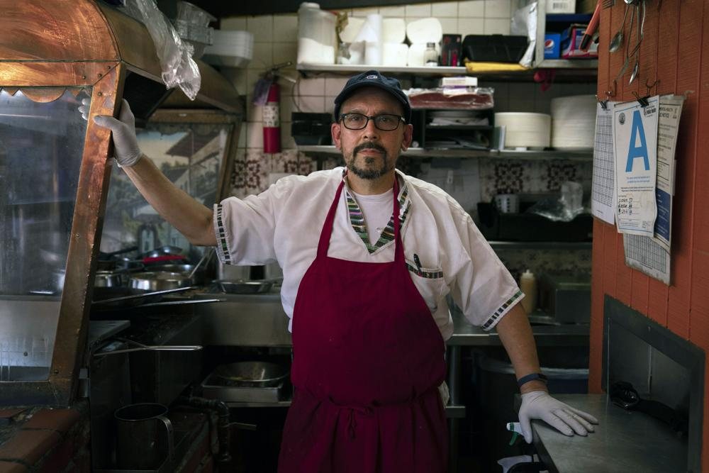 Edward Flores, 56, a fourth-generation owner of Juanita's Cafe on Olvera Street, stands for a photo in his restaurant in Los Angeles, Friday, June 4, 2021. (AP Photo/Jae C. Hong)