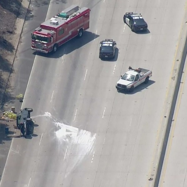 The northbound Hollywood Freeway was closed in North Hollywood after a pickup carrying pool-cleaning chemicals crashed and overturned on July 16, 2021. (KTLA)