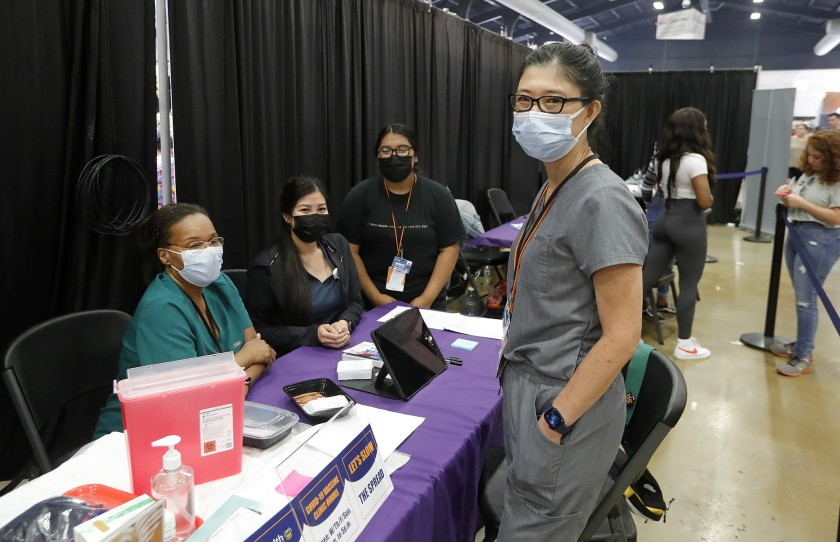 Maxim Healthcare Services site manager Karen Hsu, right, with her team at the 2021 O.C. Fair for any walk-up guests who qualify for a vaccine. (Don Leach / L.A. Times Community News )