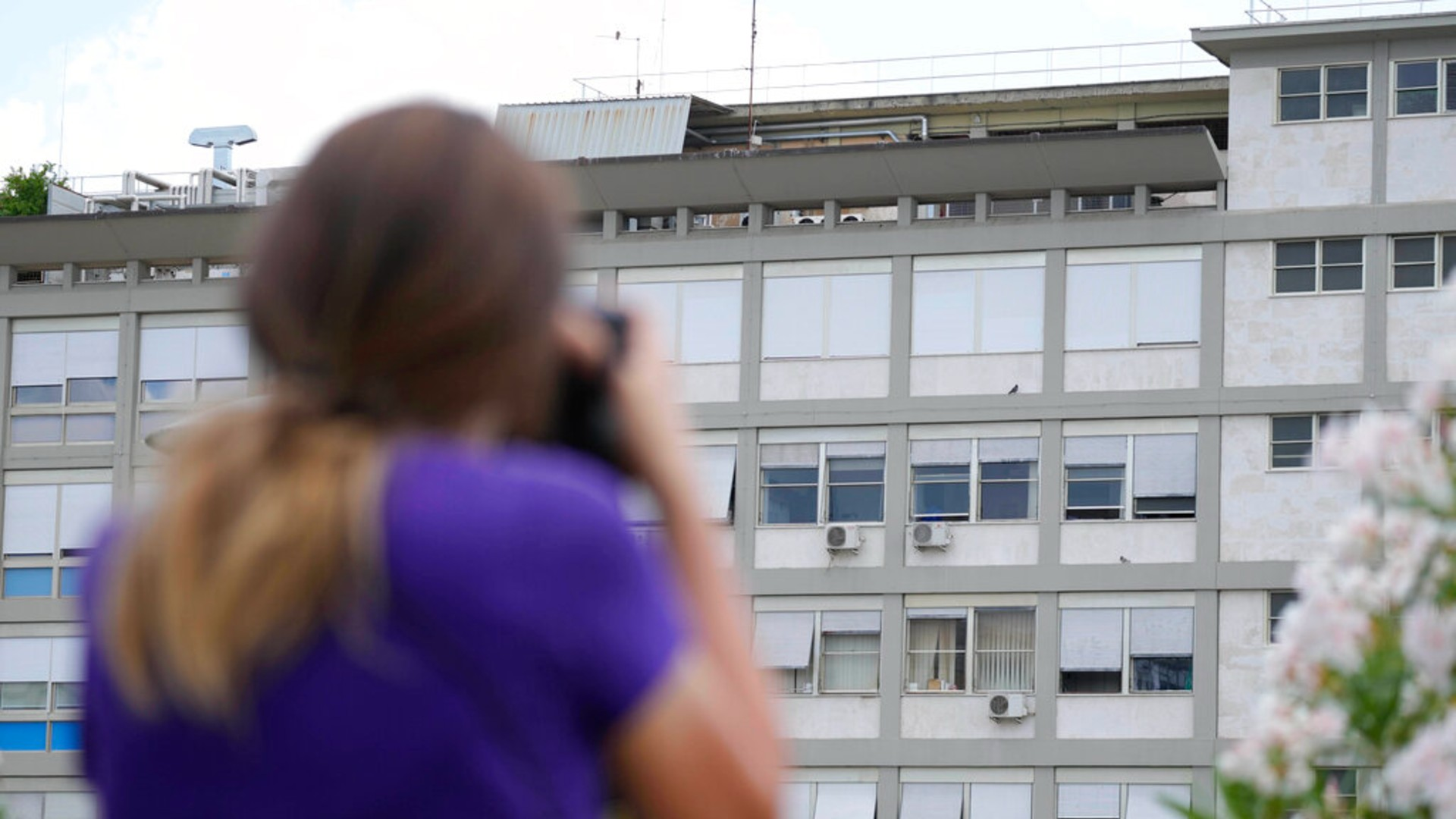 A press photographer aims her lens at the 10th floor of the Agostino Gemelli hospital, where Pope Francis was hospitalized Sunday, in Rome, Friday, July 9, 2021. (AP Photo/Gregorio Borgia)