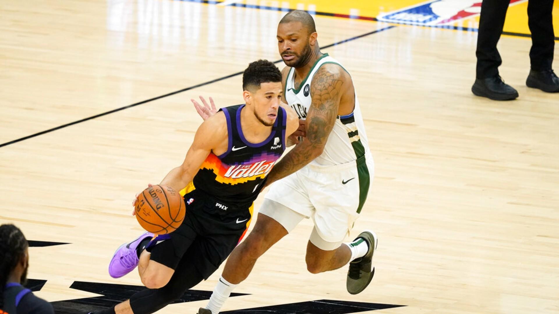 Phoenix Suns guard Devin Booker, left, dribbles against Milwaukee Bucks forward P.J. Tucker during the first half of Game 2 of basketball's NBA Finals, Thursday, July 8, 2021, in Phoenix. (AP Photo/Matt York)