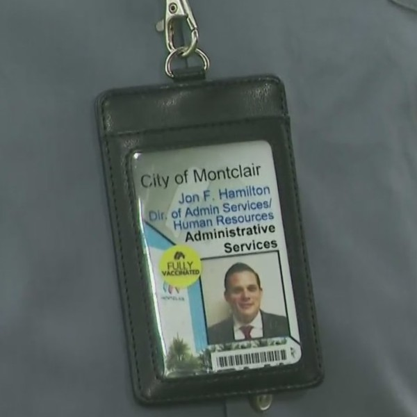 """A """"fully vaccinated"""" sticker is seen on the identification card of Montclair Director of Administrative Services and Human Resources Jon Hamilton. (KTLA)"""