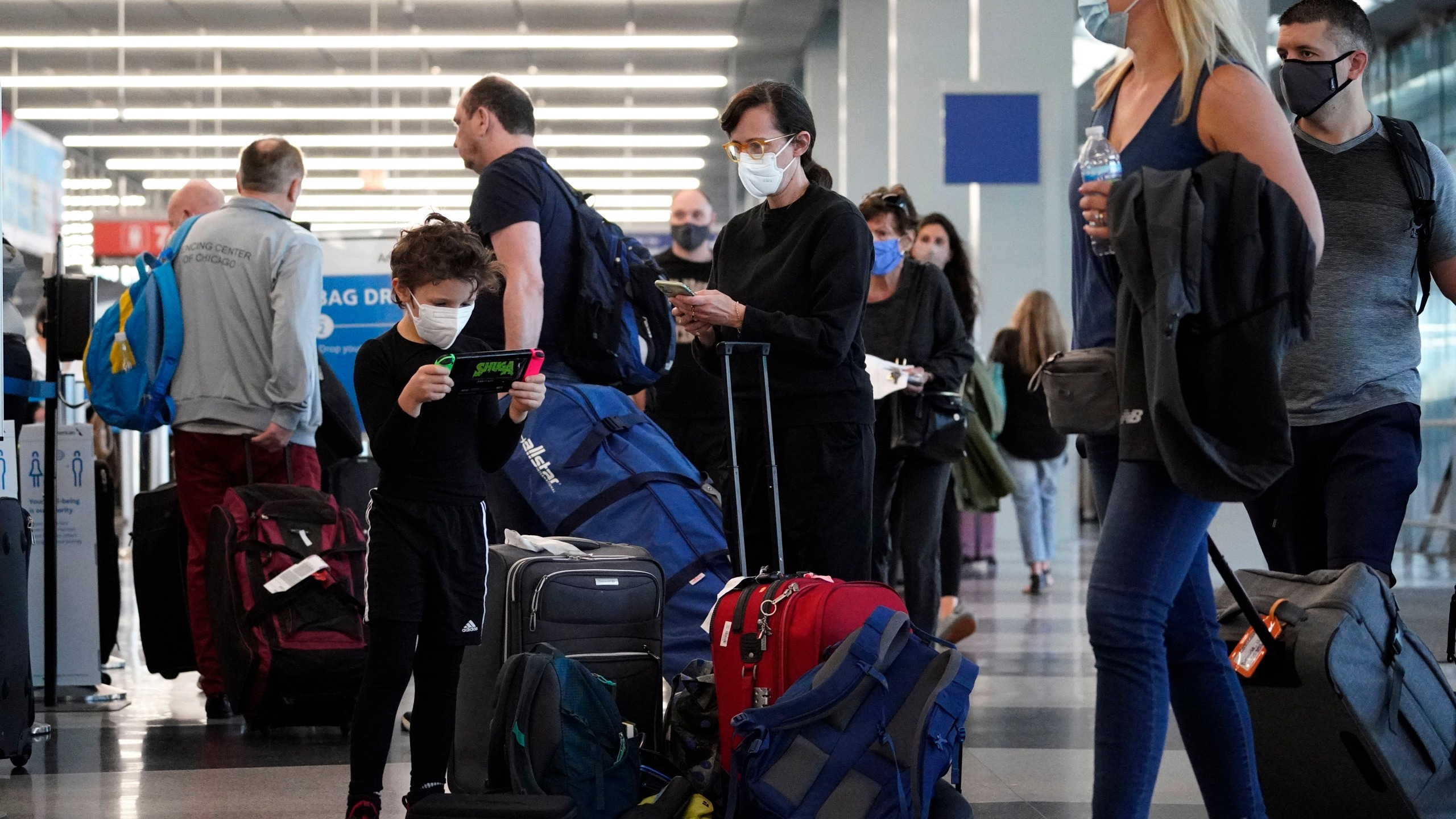 Travelers are lining up at O'Hare airport in Chicago, Friday, July 2, 2021. (AP Photo/Nam Y. Huh)