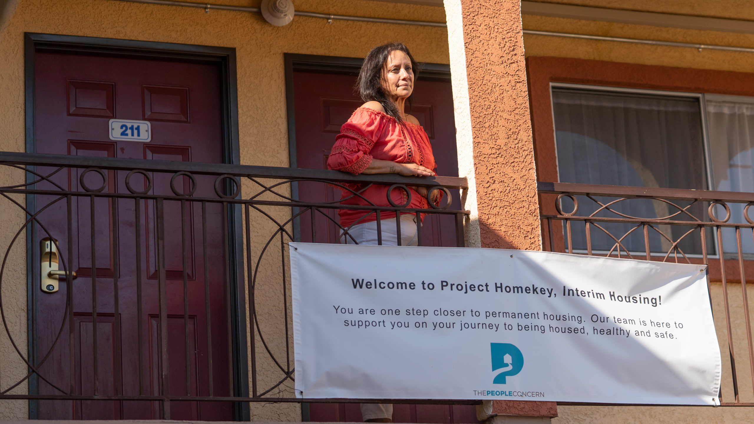 In this Wednesday, June 30, 2021, photo Veronica Perez poses outside her new home at the Mollie Mason Project Homekey site in Los Angeles. (AP Photo/Damian Dovarganes)