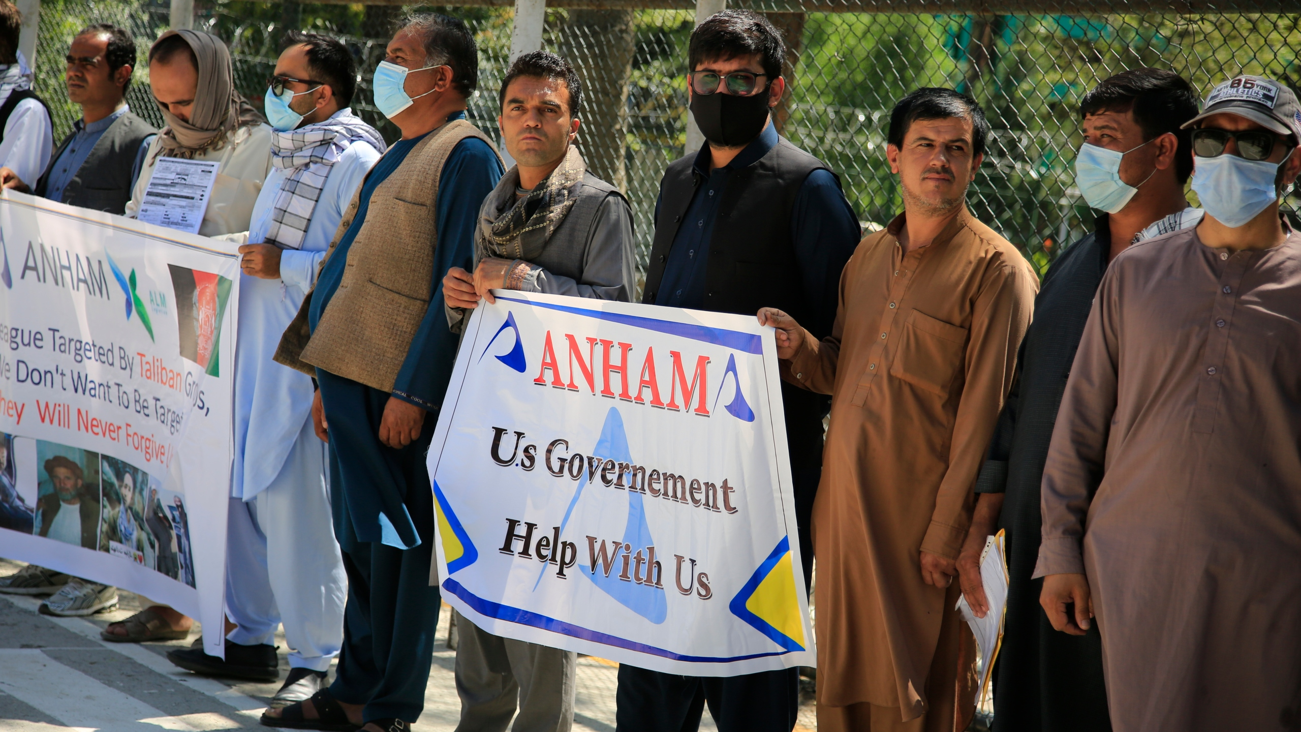 Former workers who had been employed with U.S. troops at the Bagram airbase hold placards during a demonstration against the U.S. government in Kabul, Afghanistan on July, 9, 2021. (Mariam Zuhaib/Associated Press)