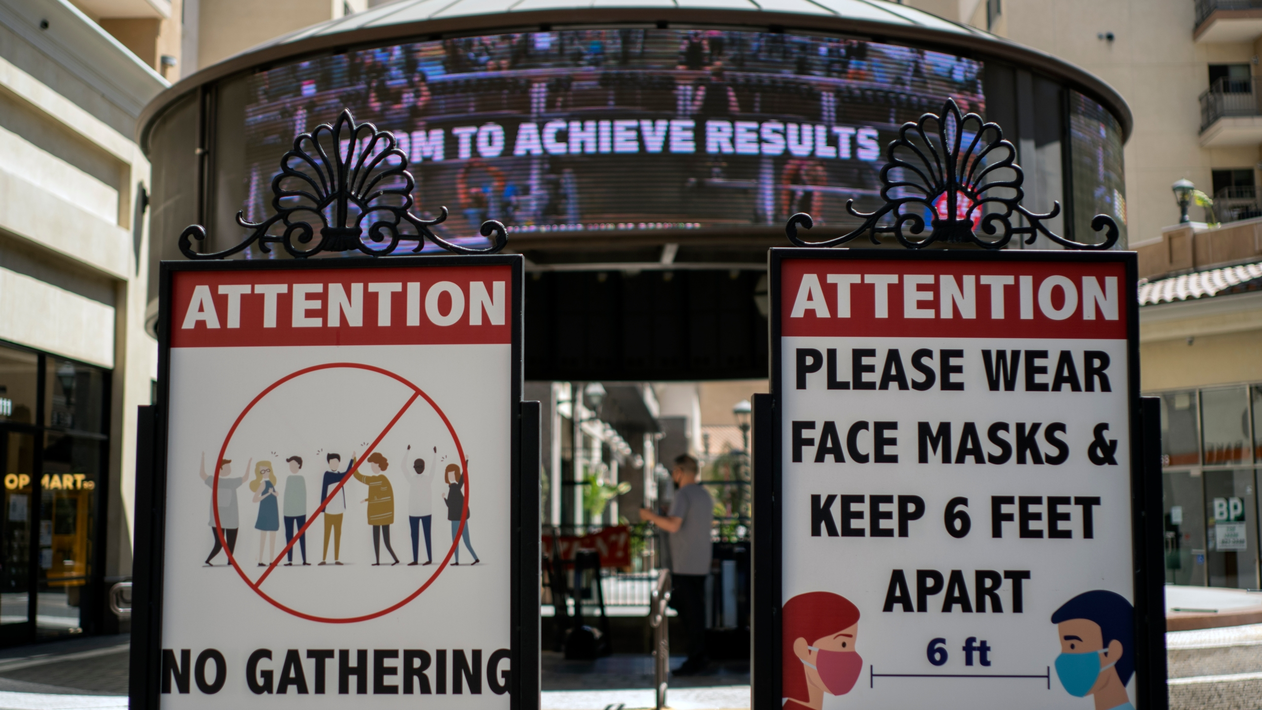 In this June 11, 2021, file photo, signs with social distancing guidelines and face mask requirements are posted at an outdoor mall amid the COVID-19 pandemic in Los Angeles. (AP Photo/Damian Dovarganes, File)