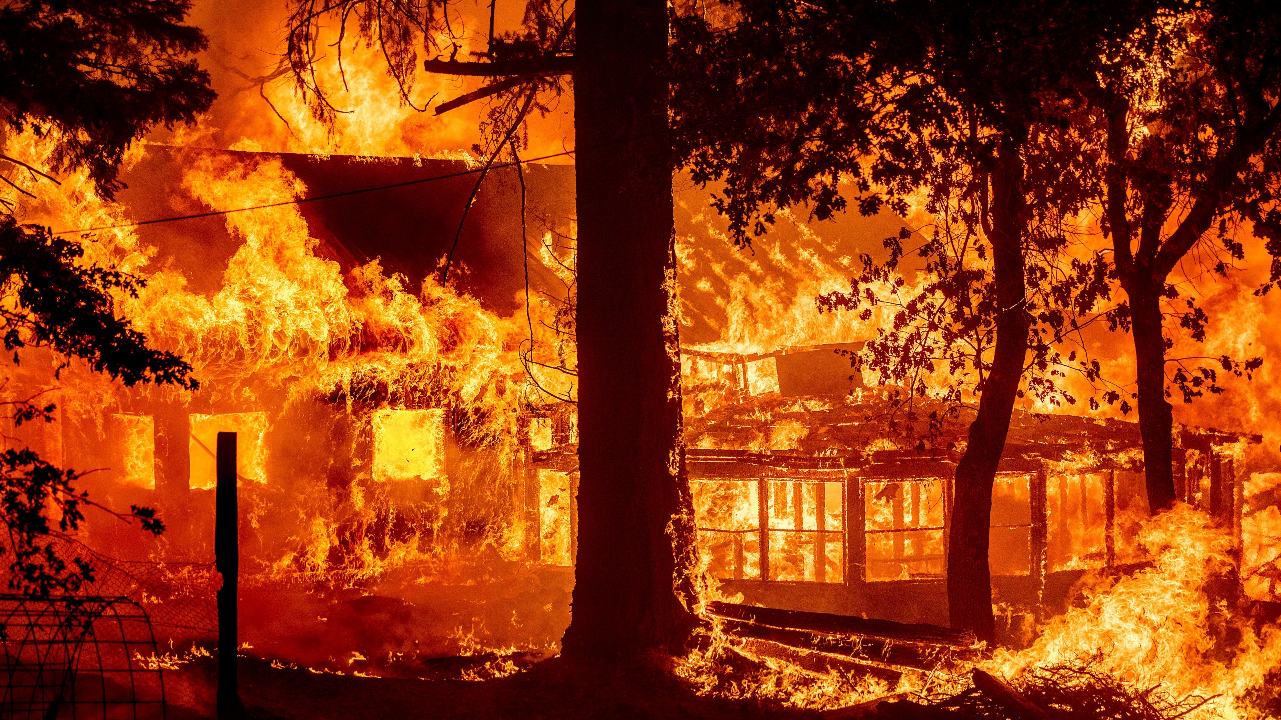 Flames from the Dixie Fire consume a home in the Indian Falls community of Plumas County, Calif., Saturday, July 24, 2021. (AP Photo/Noah Berger)