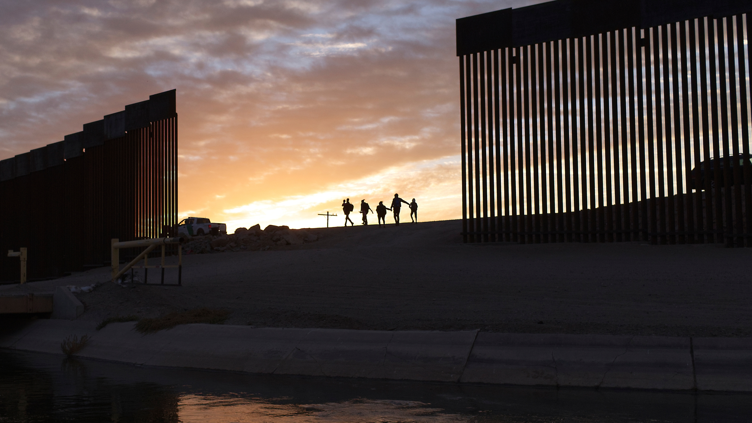 In this June 10, 2021, file photo, a pair of migrant families from Brazil pass through a gap in the border wall to reach the United States after crossing from Mexico to Yuma, Ariz., to seek asylum. (AP Photo/Eugene Garcia, File)