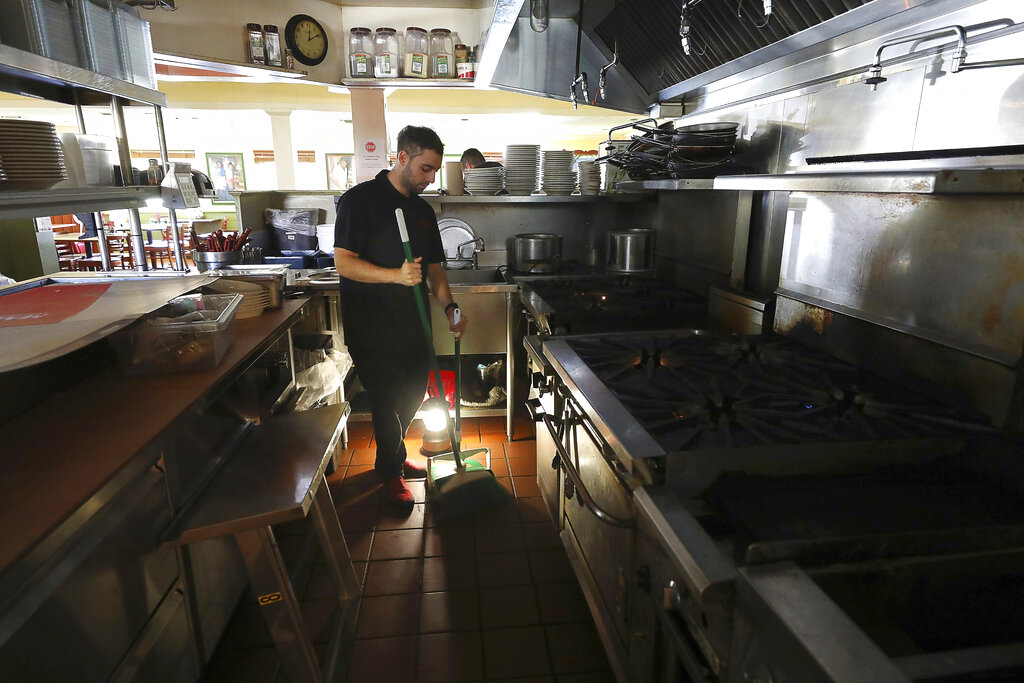 In this Oct. 10, 2019, file photo, Salvador Espinosa sweeps in the kitchen of a Mary's Pizza Shack restaurant during a Pacific Gas & Electric power shutdown in Santa Rosa, Calif. (Christopher Chung//The Press Democrat via AP, FIle)