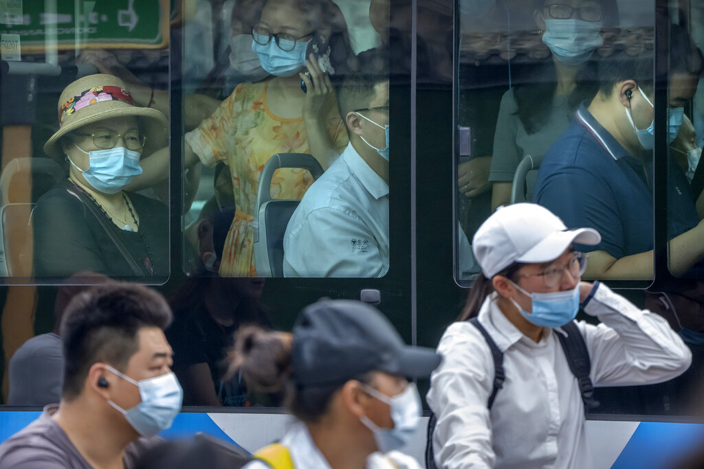 People wearing face masks to protect against COVID-19 ride on a bus during the morning rush hour in Beijing, Wednesday, Aug. 4, 2021. (AP Photo/Mark Schiefelbein)