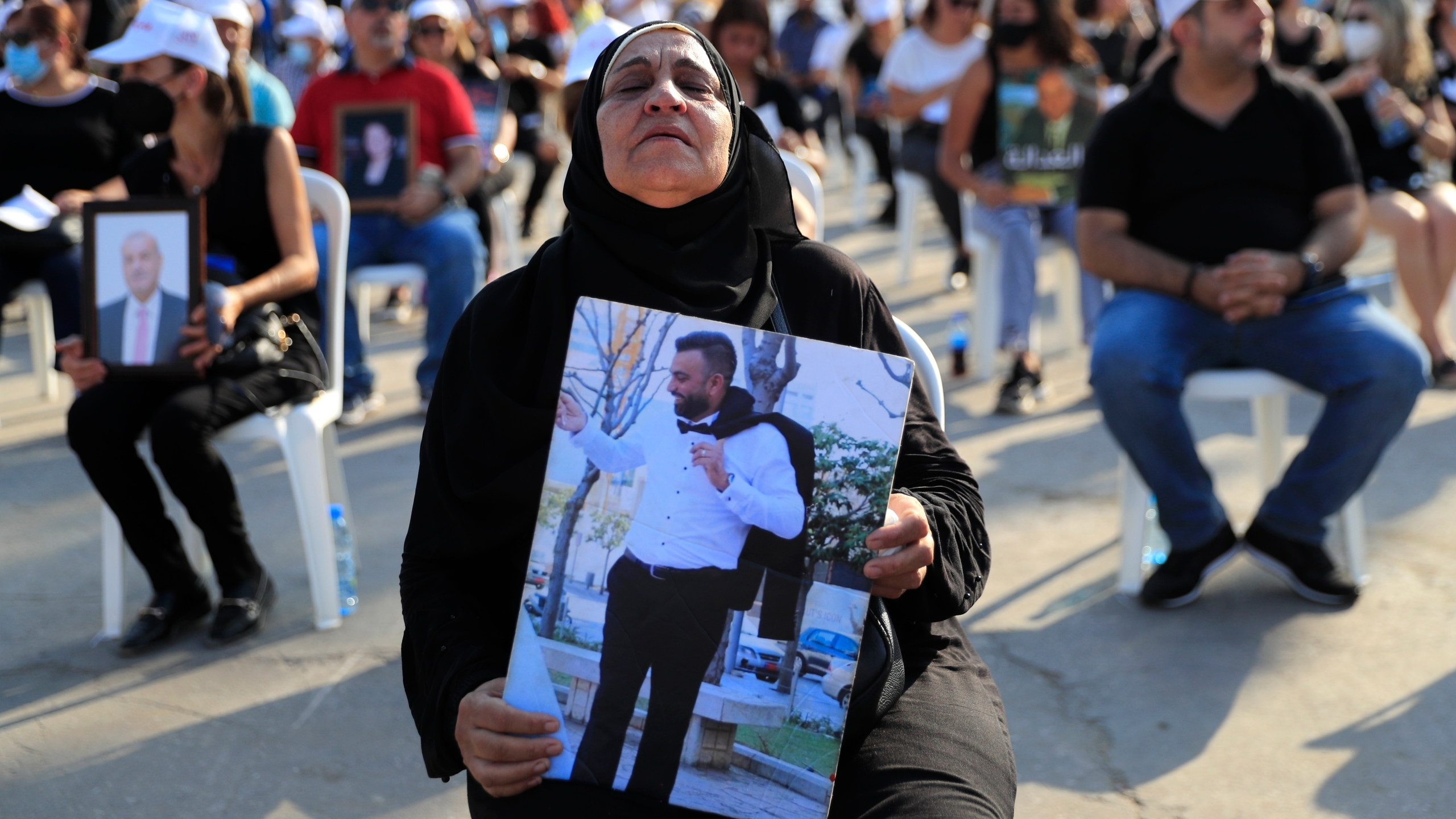 The mother of a victim who was killed in the massive blast last year at the Beirut port holds a portrait of her son as she attends a Mass held to commemorate the first year anniversary of the deadly blast, at the Beirut port in Lebanon on Aug. 4, 2021. United in grief and anger, families of the victims and other Lebanese came out into the streets of Beirut on Wednesday to demand accountability as banks, businesses and government offices shuttered to mark one year since the horrific explosion. (AP Photo/Hussein Malla)