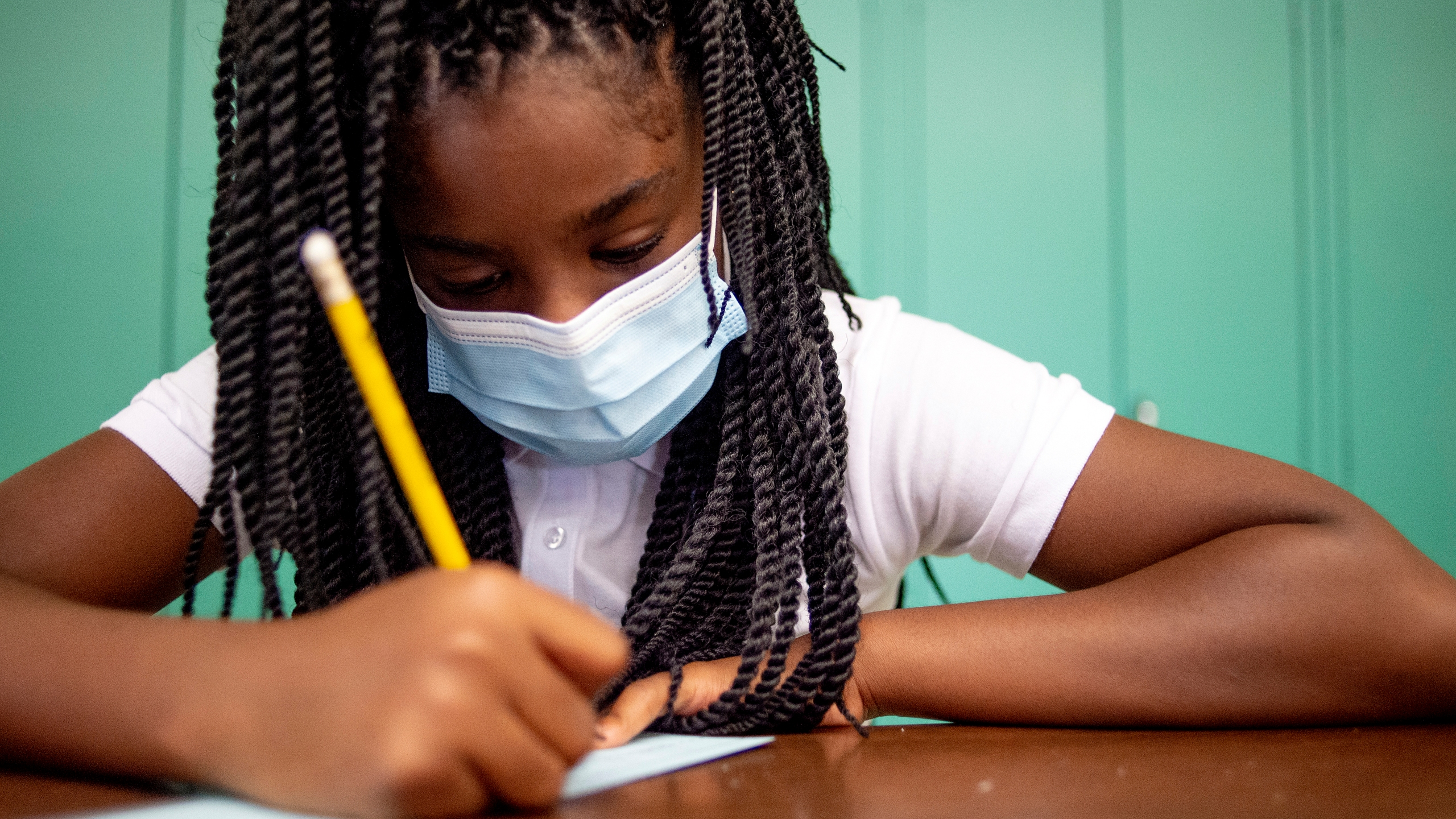 Sixth-grader Adriana Campbell, 11, jots down her name as she starts to work on her first assignment during the first day of school on Wednesday, Aug. 4, 2021 at Freeman Elementary School in Flint, Mich. (Jake May/The Flint Journal via AP)
