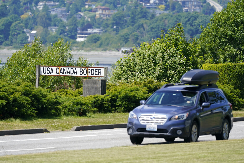 In this June 8, 2021, file photo, a car heads into the U.S. from Canada at the Peace Arch border crossing in Blaine, Wash. (AP Photo/Elaine Thompson, File)