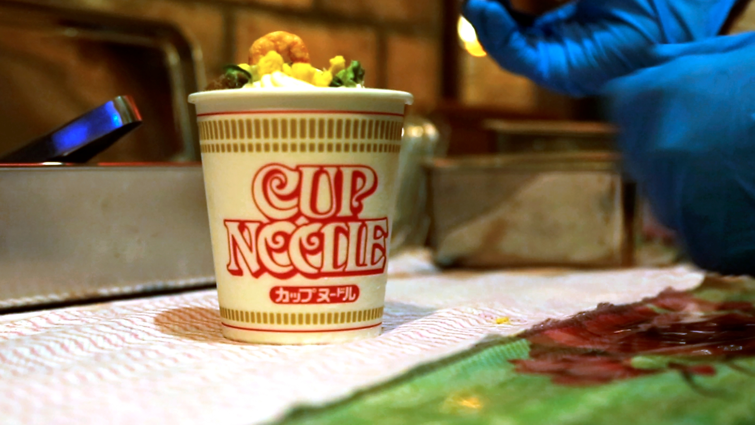 A Cup Noodle ice cream, made with the powdered soup of Cup Noodle and topped with freeze-fried shrimp, onions, egg and meat, is prepared to be eaten at the Cup Noodles Museum in Yokohama, Japan, on Friday, Aug. 6, 2021. Sold only at the Yokohama museum, the ice cream embodies a spirit of adventure in Japanese foods. (AP Photo/John Leicester)