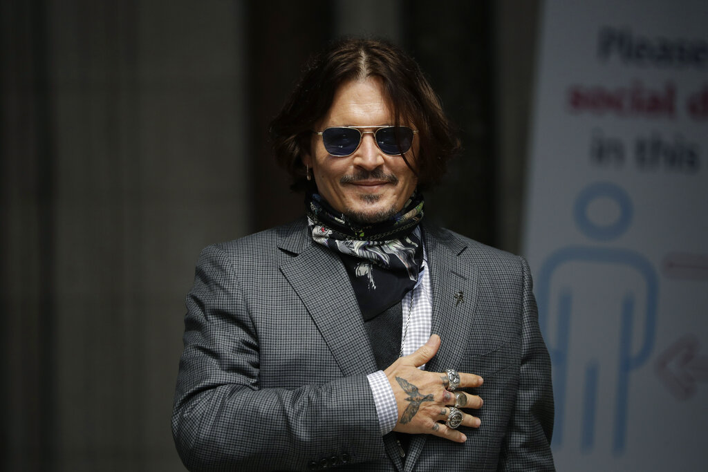 In this Thursday, July 23, 2020 file photo, U.S. actor Johnny Depp gestures to fans and the media as he arrives at the High Court in London. (AP Photo/Matt Dunham, file)