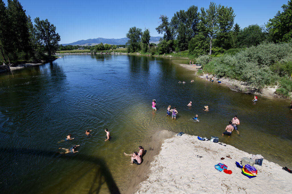 In this June 30, 2021 file photo Missoulians cool off in the Bitterroot River as temperatures crested 100 degrees Fahrenheit in Missoula, Mont. (AP Photo/Tommy Martino, File)