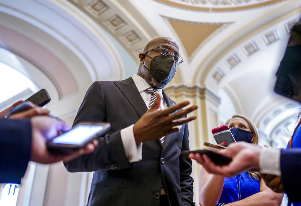 Sen. Raphael Warnock, D-Ga., a key figure on voting rights efforts, speaks to reporters after a huddle with other Democrats as they look to salvage their push to enact voting rights legislation, at the Capitol in Washington, Tuesday, Aug. 10, 2021. (AP Photo/J. Scott Applewhite)