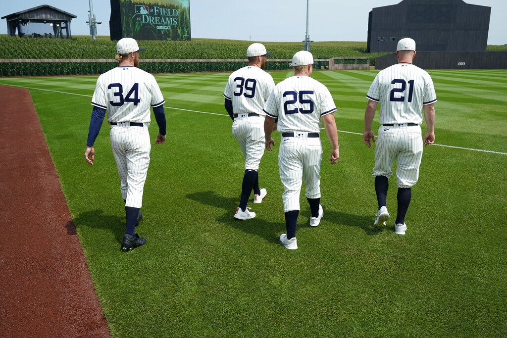 Chicago White Sox players Michael Kopech (34), Aaron Bummer (39), Andrew Vaughn (25) and Zack Collins (21) walk on the field before a baseball game against the New York Yankees, Thursday, Aug. 12, 2021, in Dyersville, Iowa. (AP Photo/Charlie Neibergall)