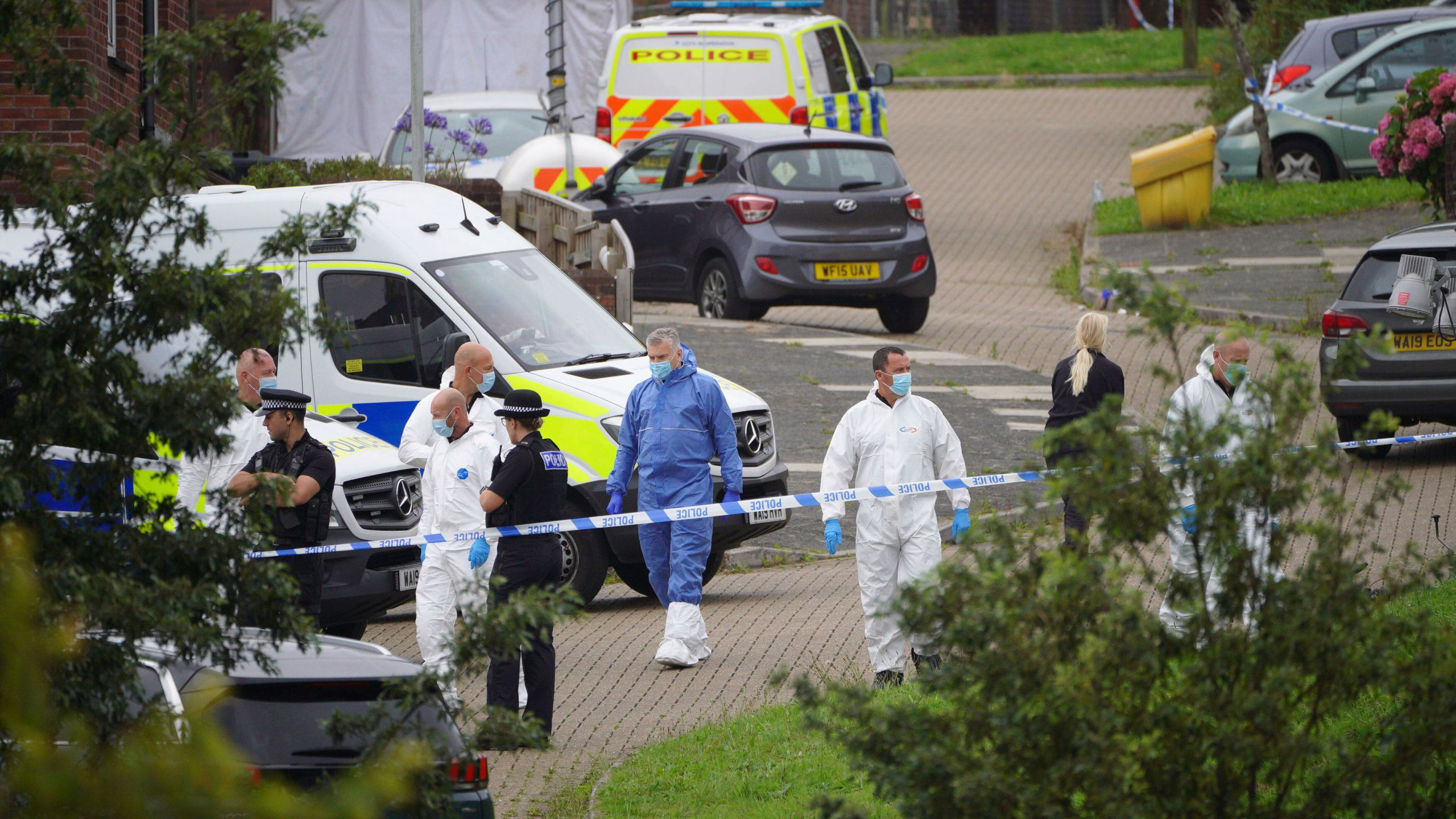 Forensic officers walk in Biddick Drive in the Keyham area of Plymouth, England Friday Aug. 13, 2021 where six people were killed in a shooting incident. (Ben Birchall/PA via AP)