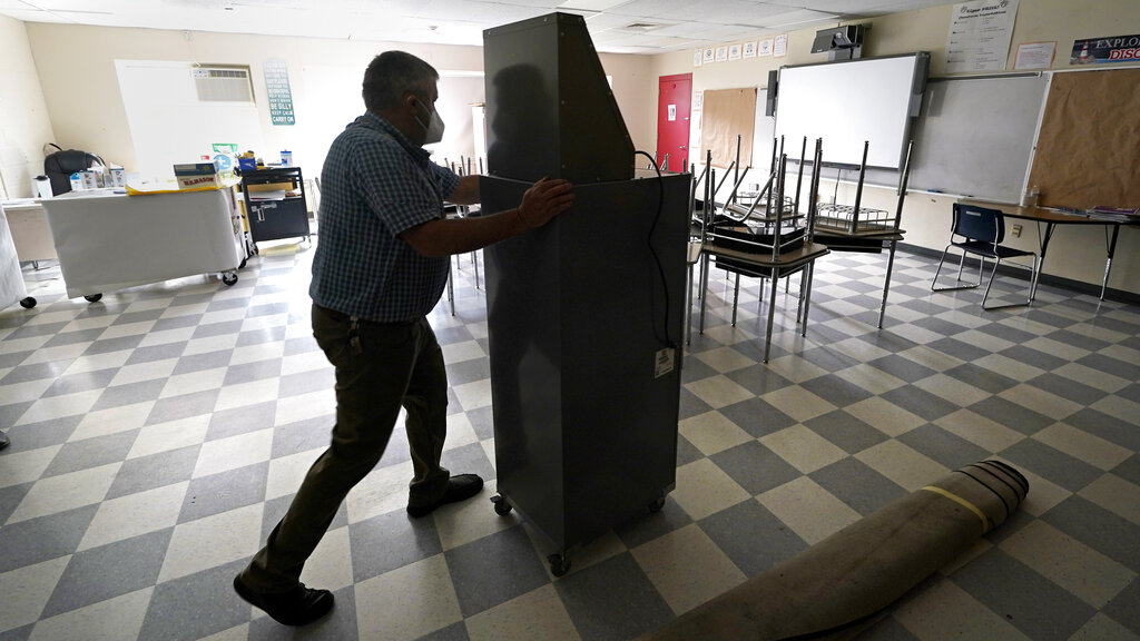 Whitney Anderson wheels a recently purchased air scrubber through a classroom in advance of the school year at the E.N. White School in Holyoke, Mass., on Wednesday, Aug. 4, 2021. (AP Photo/Charles Krupa)